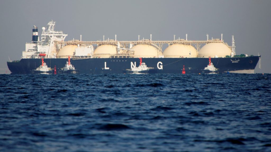 An LNG tanker is tugged towards a thermal power station in Futtsu