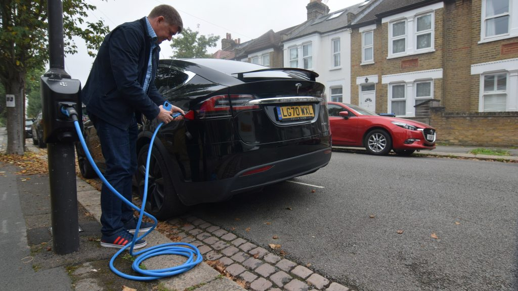 Richard Stobart, CEO of an electric vehicle charging system startup company Char.gy, demonstrates one of the company's lamp post chargers in London